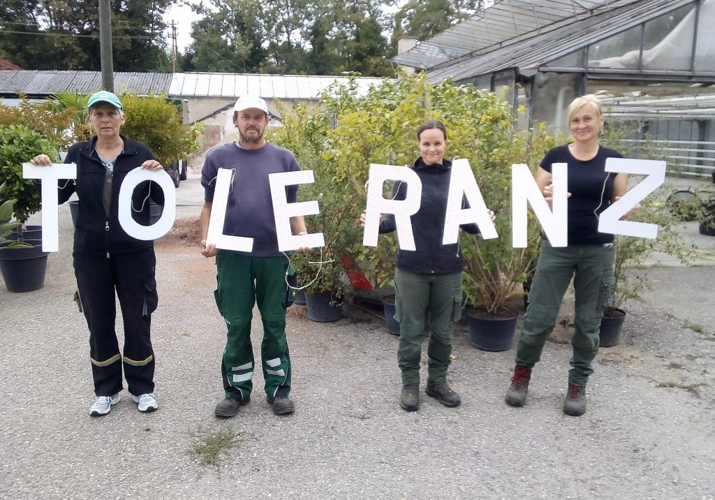 Der Begriff Toleranz dargestellt mit Holzbuchstaben und gehalten von Mitarbeiter*innen der Stadtgärtnerei Wiesloch