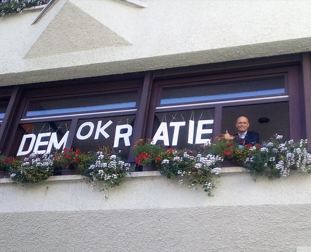 Der Begriff Demokratie dargestellt in Holzbuchtaben im Fenster des Büros des Wieslocher Oberbürgermeisters Elkemann