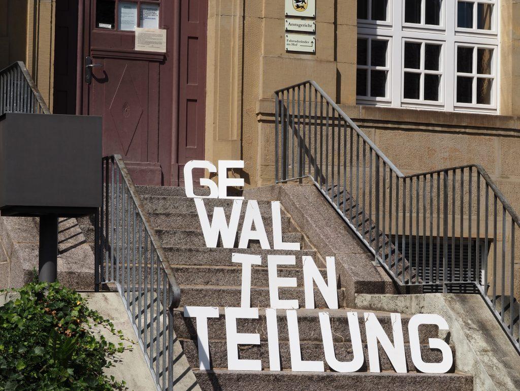 Der Begriff Gewaltenteilung dargestellt in Holzbuchstaben auf der Treppe des Wieslocher Amtsgerichts