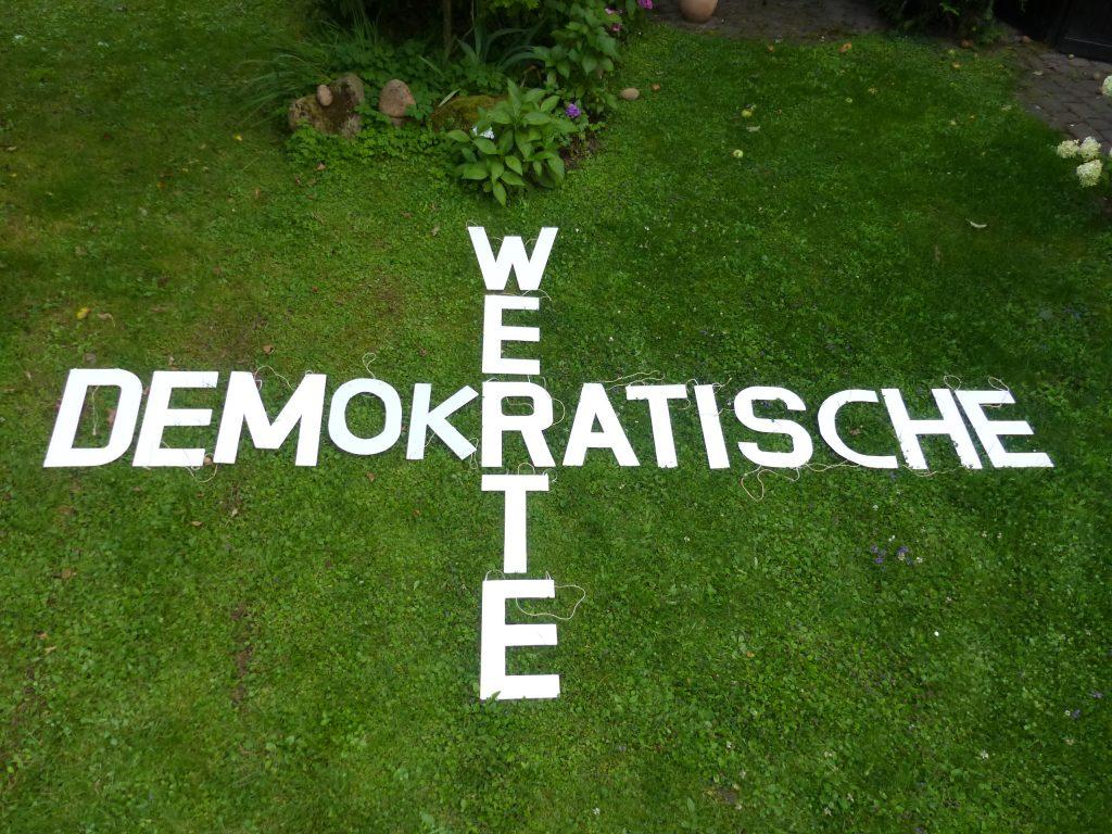 Die Begriffe Demokratische Werte dargestellt mit Holzbuchstaben im Gras liegend