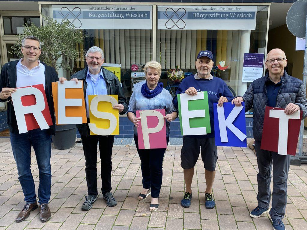 """Mitglieder der Bürgerstiftung halten den Begriff """"Respekt"""" mittels Holzbuchstaben"""